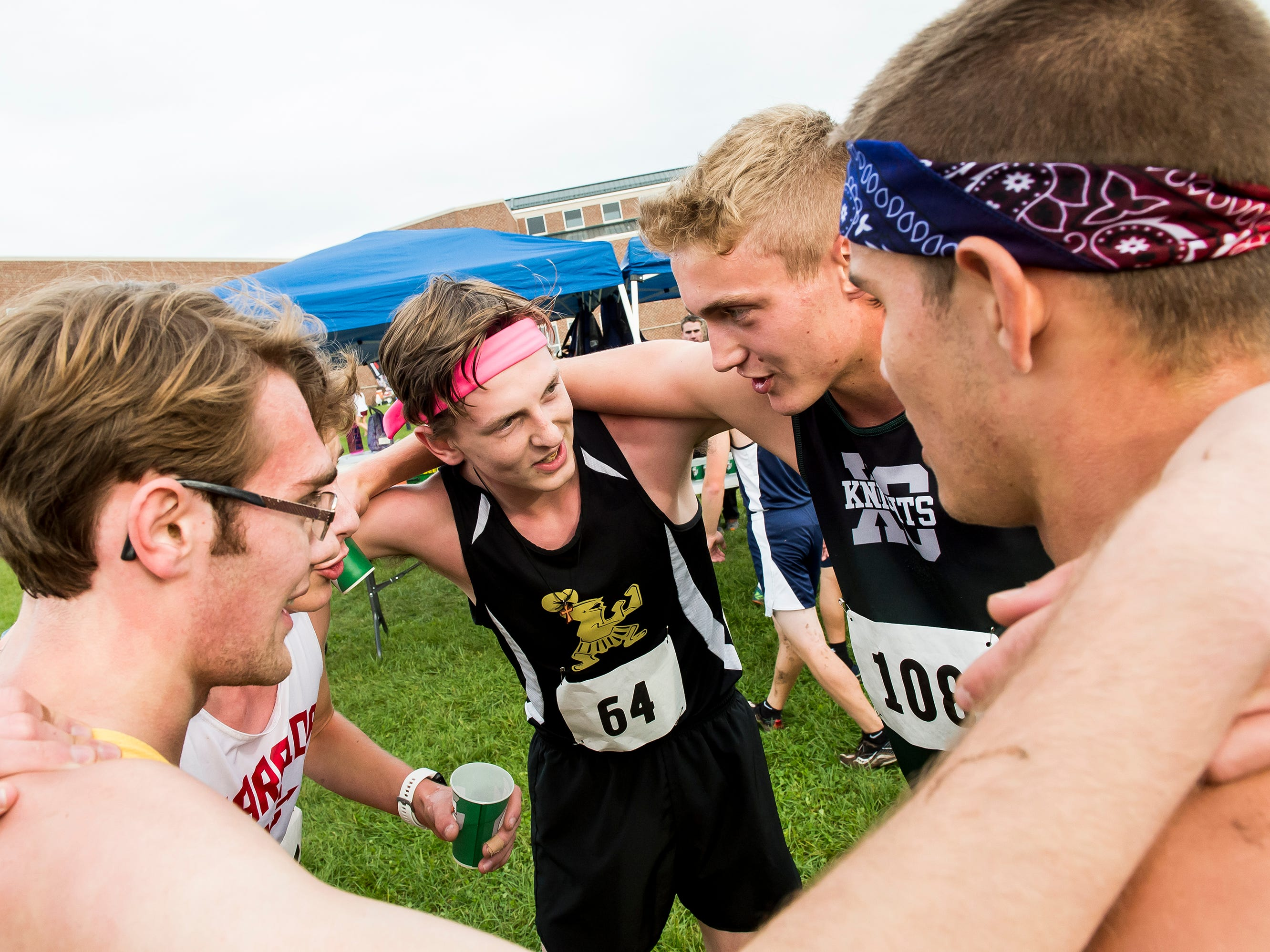 A group of runners huddle up after competing in the YAIAA cross country championships at Gettysburg Area High School on Tuesday, October 16, 2018.