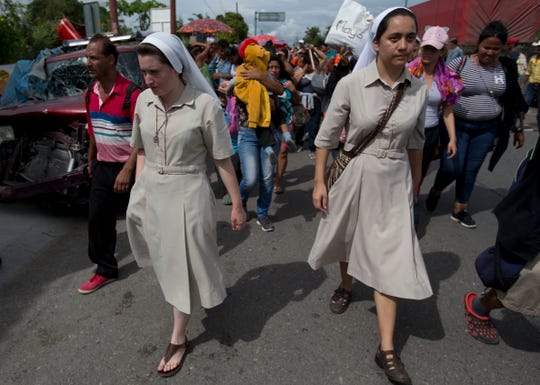 A couple of nuns accompany Honduran migrants as they arrive Oct. 16 in Chiquimula, Guatemala, on their way to the United States. U.S. President Donald Trump threatened to cut aid to Honduras if the impromptu caravan of migrants isn't stopped.