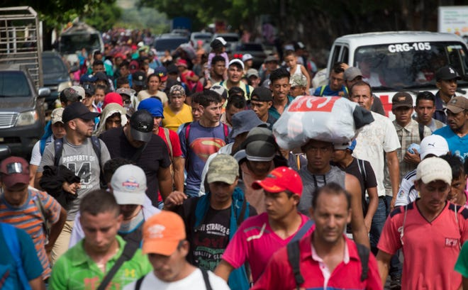 Honduran migrants walk toward the United States. as they arrive at Chiquimula, Guatemala on Oct. 16, 2018. U.S. President Donald Trump threatened to cut aid to Honduras if the nation doesn't stop the impromptu caravan of migrants.