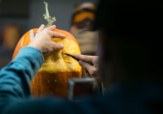 World-renowned pumpkin carver Ray Villafane carves a face into a pumpkin while getting ready for Carfree's Enchanted Pumpkin Garden. The garden opens October 19 and runs through October 28.