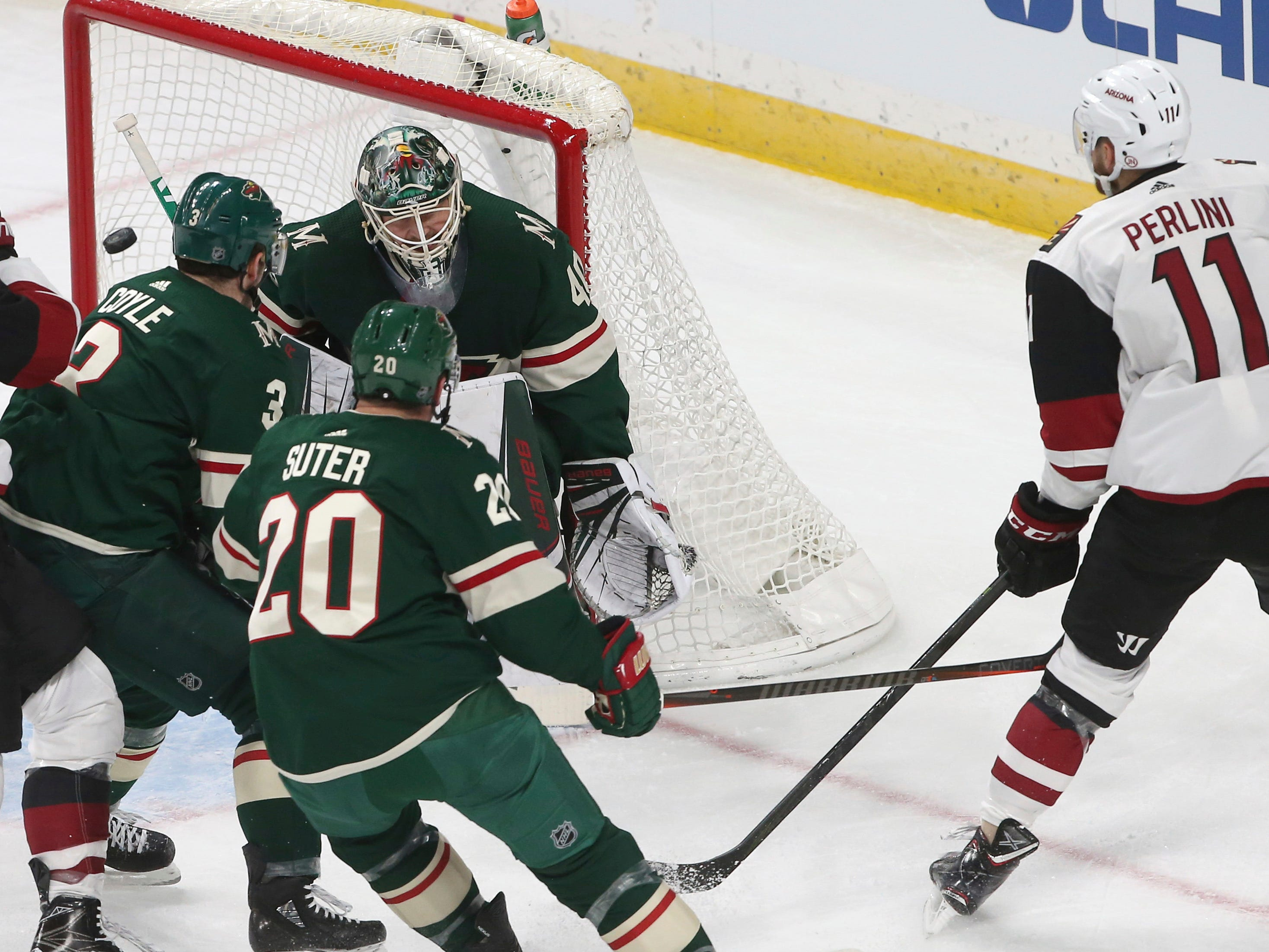 Arizona Coyotes' Brendan Perlini, right, of Great Britain, watches his power play goal off Minnesota Wild's goalie Devan Dubnyk in the first period of an NHL hockey game Tuesday, Oct. 16, 2018, in St. Paul, Minn.