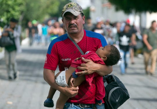 A Honduran migrant carries his son in Chiquimula, Guatemala, on Oct. 16, 2018, as he heads toward the United States. U.S. President Donald Trump threatened to cut aid to Honduras if it doesn't stop the migrant caravan.