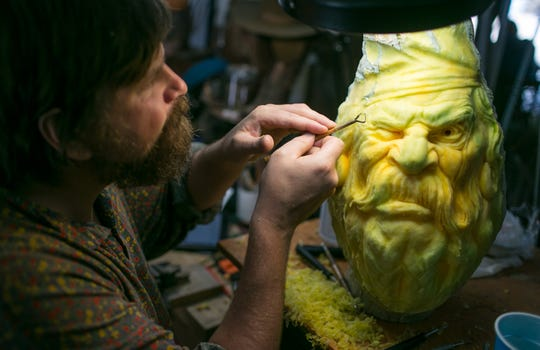 Artist Dmitry Klimenko, of Russia, works on carving a face into a pumpkin at the Villafane Studios in Carefree. Villafane, a world-renowned pumpkin carver, employee talented carvers to create artwork for Carfree's Enchanted Pumpkin Garden. The garden opens October 19 and runs through October 28.