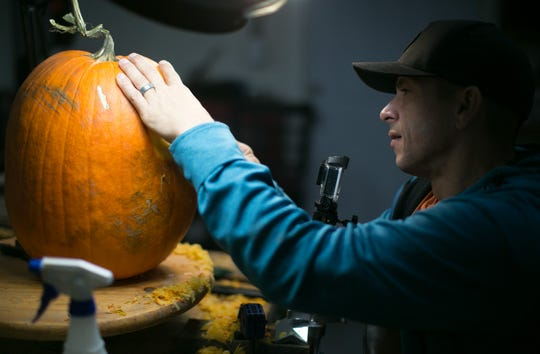 World-renowned pumpkin carver Ray Villafane carves a face into a pumpkin while getting ready for Carfree's Enchanted Pumpkin Garden. The garden opens October 19 and runs through October 28.