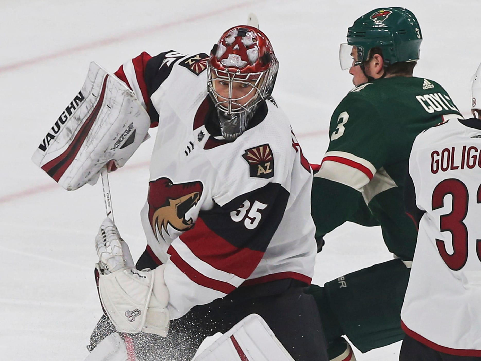Arizona Coyotes' goalie Darcy Kuemper, left, leaves the net to clear a puck away from Minnesota Wild's Charlie Coyle in the first period of an NHL hockey game Tuesday, Oct. 16, 2018, in St. Paul, Minn.