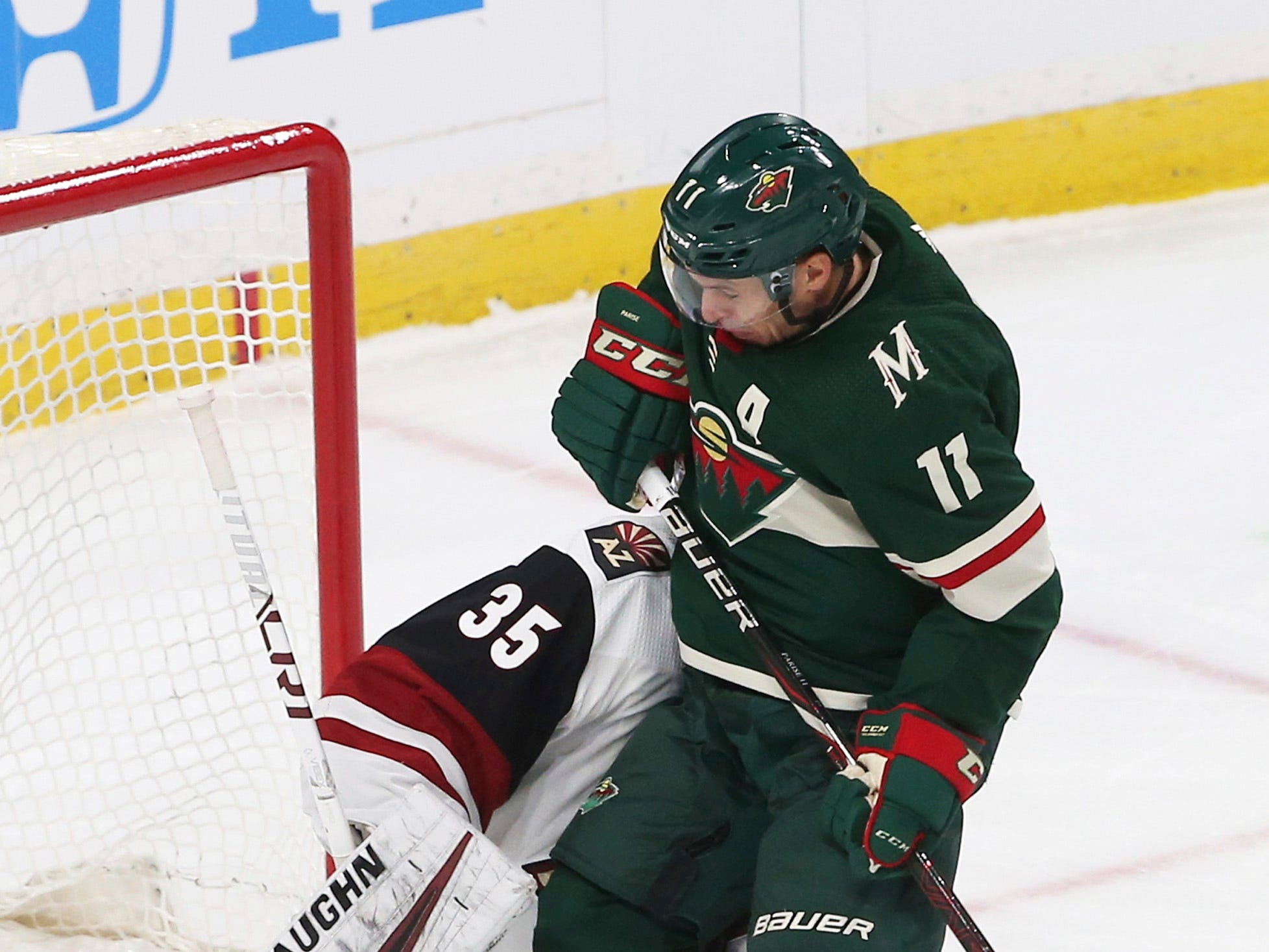 Minnesota Wild's Zach Parise, right, jumps clear and into Arizona Coyotes' goalie Darcy Kuemper to make way for a shot in the first period of an NHL hockey game Tuesday, Oct. 16, 2018, in St. Paul, Minn.