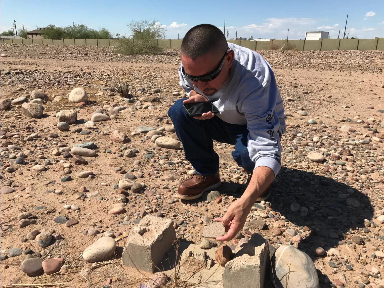 Tim Díaz, quien creció en el vecindario Sotelo-Heard, examina los restos de una lápida que fue destrozada hace años.