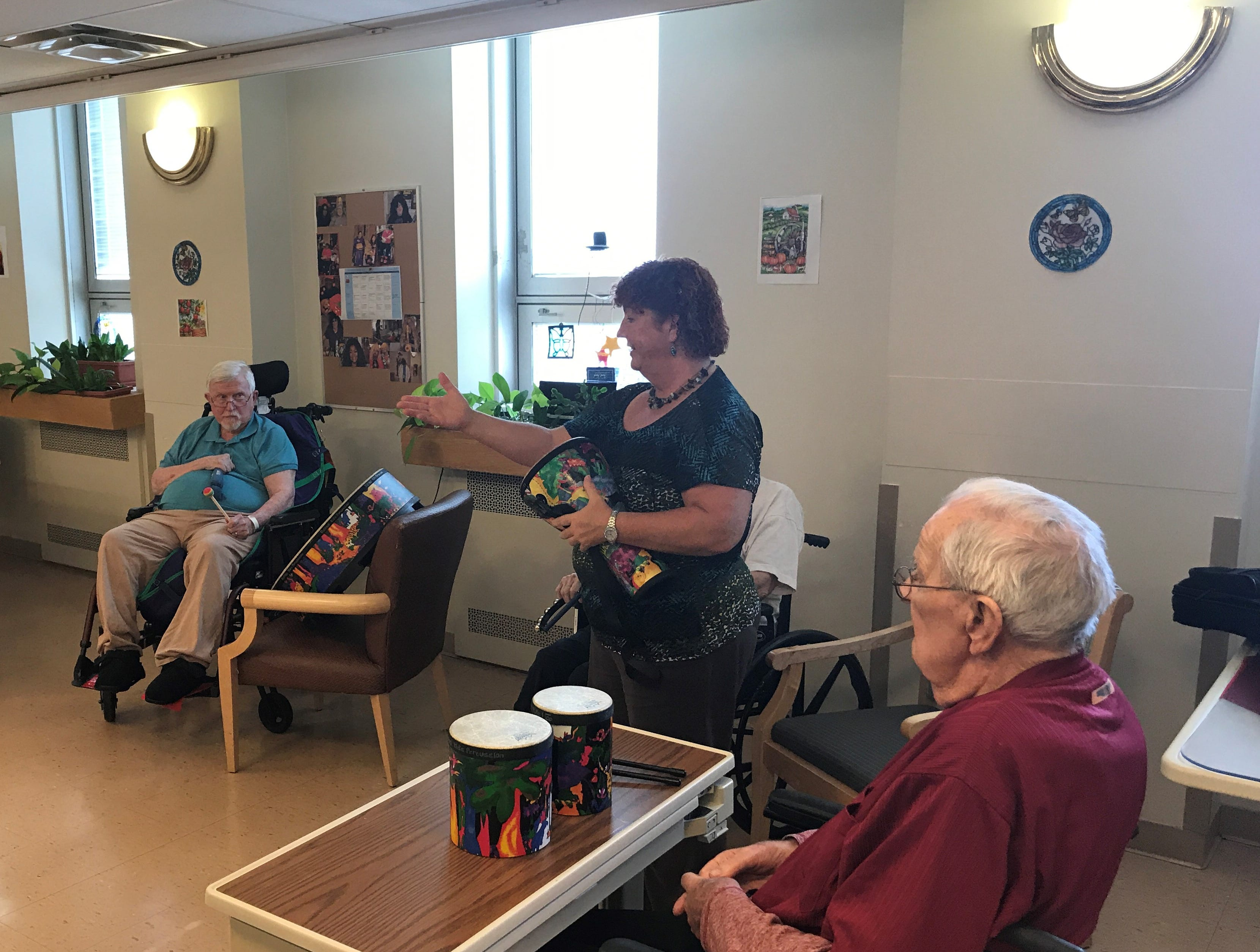 Recreational therapist Sybil Stambaugh leads a drum circle for veterans and Cedar Crest students at the Lebanon VA Medical Center on Oct. 17, 2018.