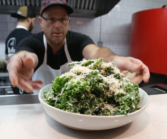 Coo Robert Capano finishes preparing a kale salad at Lolita's in the City of Poughkeepsie on October 16, 2018.