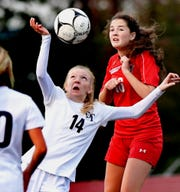 Dallastown's Ashley Robinson, foreground, heads the ball with Susquehannock's Lilly Denis defending during quarterfinal soccer action at Northeastern High School Tuesday, October 16, 2018. Bill Kalina photo