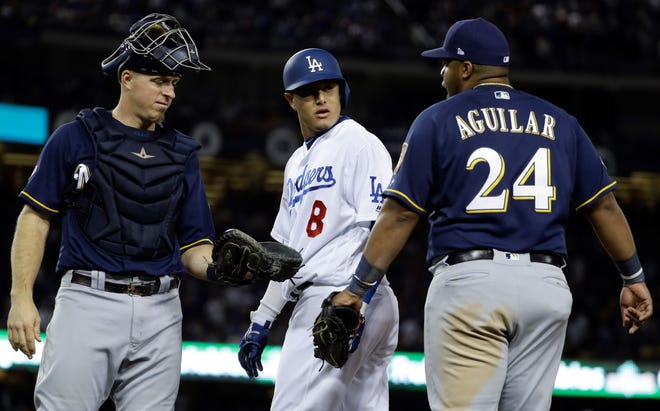 Milwaukee Brewers' Jesus Aguilar and Los Angeles Dodgers' Manny Machado have words during the 10th inning of Game 4 of the National League Championship Series baseball game Tuesday, Oct. 16, 2018, in Los Angeles. (AP Photo/Matt Slocum)