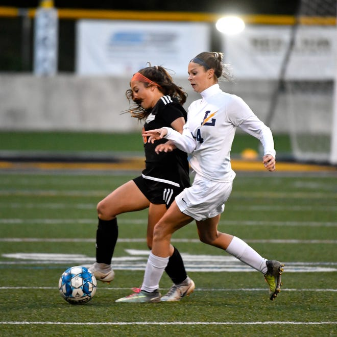 Central York's Ava Myers (10), left, tries to wrestle the ball away from Littlestown's Brayden Ball (14), right, during the girls soccer game between Littlestown and Central York, October 16, 2018. The Panthers beat the Bolts 6-1.