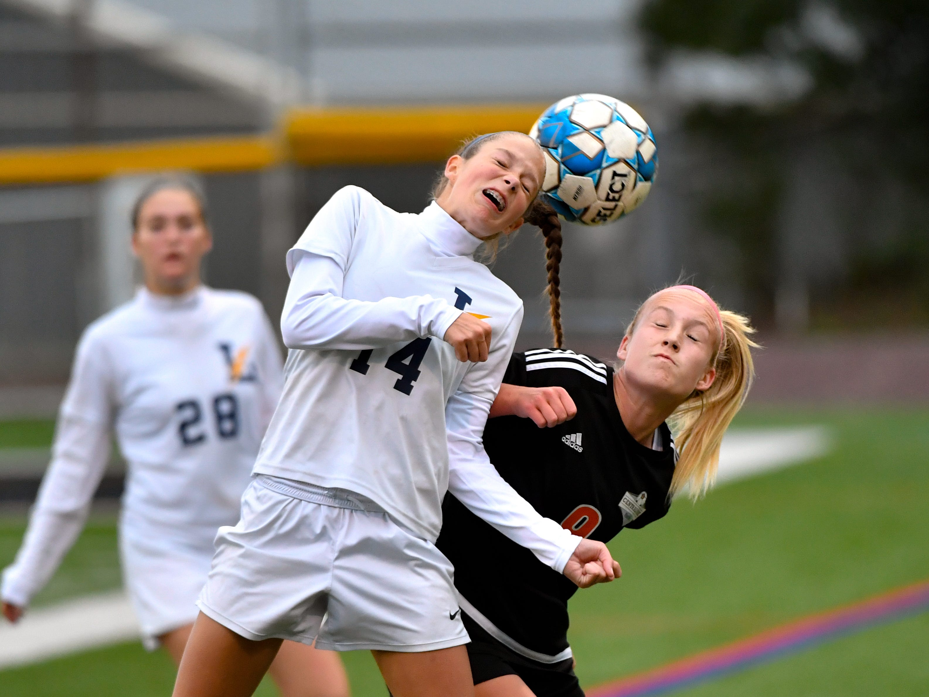 Brayden Ball (14) of Littlestown, left, wins the header over Sydney Koncsol (9), right, of Central York, October 16, 2018. The Panthers beat the Bolts 6-1.
