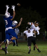 Douglas quarterback Colton Weidner throws over the out-stretched arms of Reno's Wyatt Draeger in their football game at Reno High School on Sept. 14, 2018.