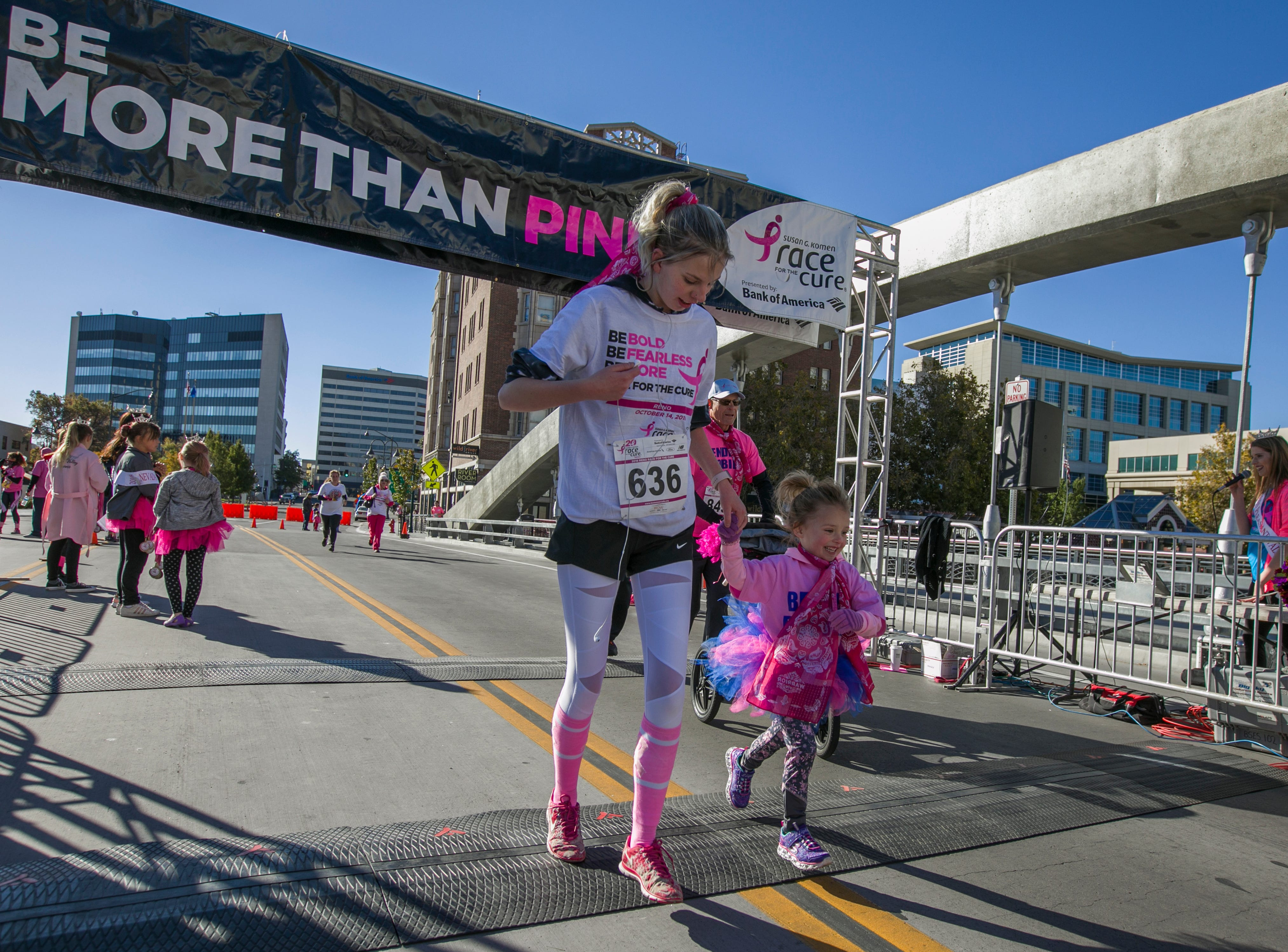 Participants cross the finish line during the Susan G. Komen Race for the Cure on Sunday, October 14,  2018 in downtown Reno.