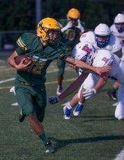 Manogue's Drew Scolari (12) runs against Reno in the first half on  September 21, 2018 at Manogue.