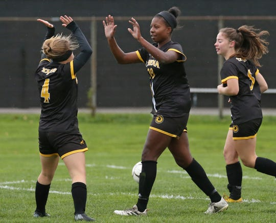Greece Athena's Waniya Hudson, center, celebrates her second goal of the game against Eastridge with teammates Isabella Tallini, left, and  Kiera Osier, right.