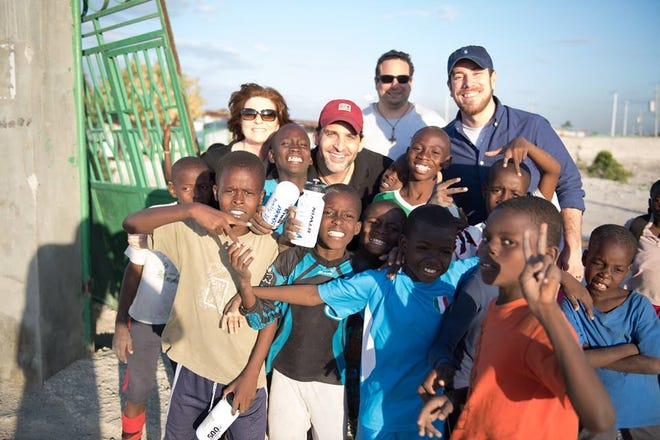 Jennifer Rayno, left, and Angelo Rose, center, smile for a photo with a group of children in Haiti.