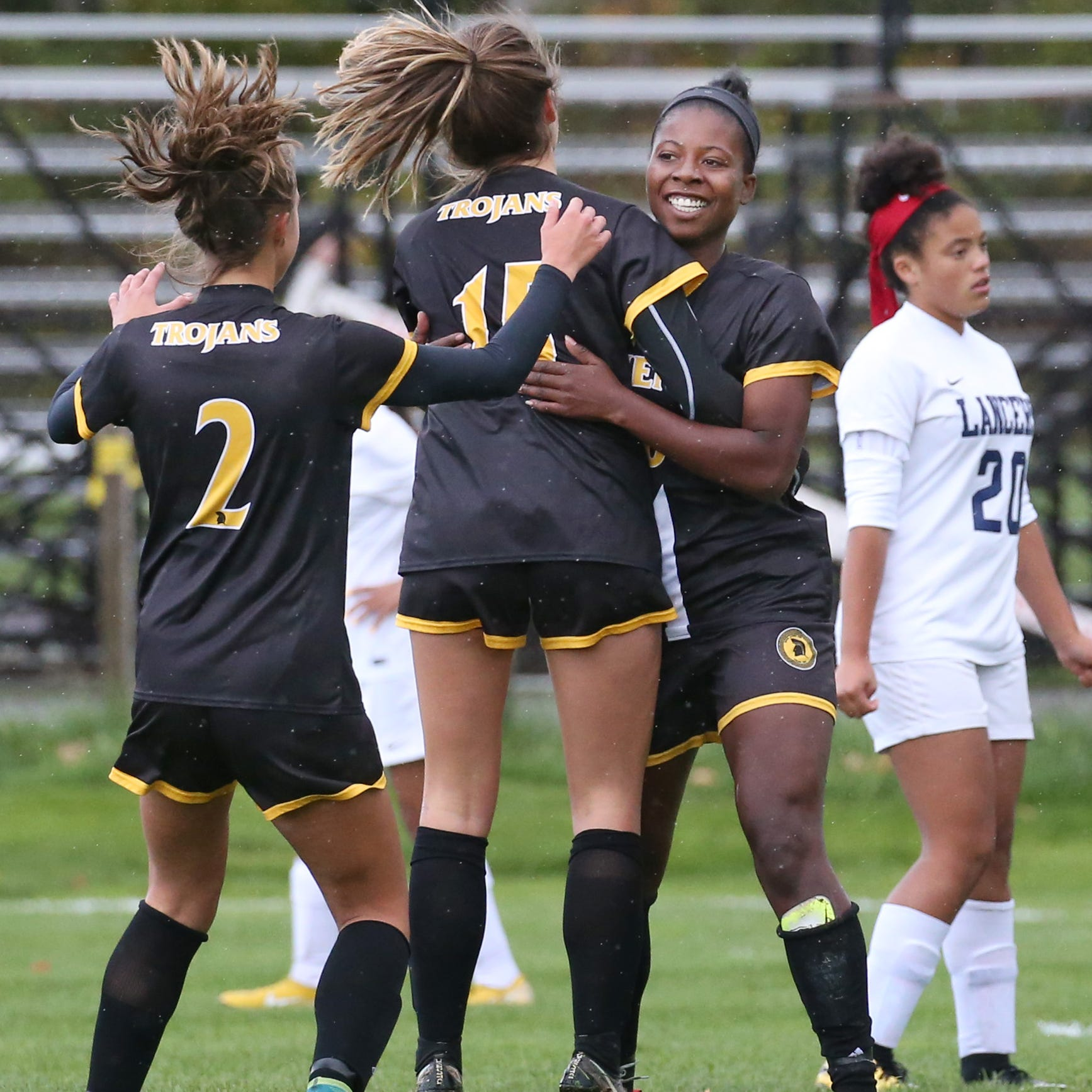 Greece Athena's Waniya Hudson, right, celebrates her first goal of the game against Eastridge with teammates Jade Talone, center, and Kelsey Nugent, left, during their Section V Class A game Wednesday, Oct. 17 at Greece Athena High School.  Hudson scored all three goals for Athena in the first half, as the Trojans raced out to a 3-0 lead.