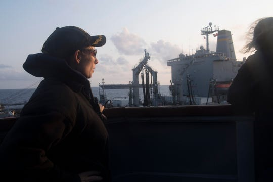Cmdr. Jamie Davidson Hopkins supervises an Underway Replenishment at Sea from the bridge wing of the guided-missile destroyer USS Wayne E. Meyer.