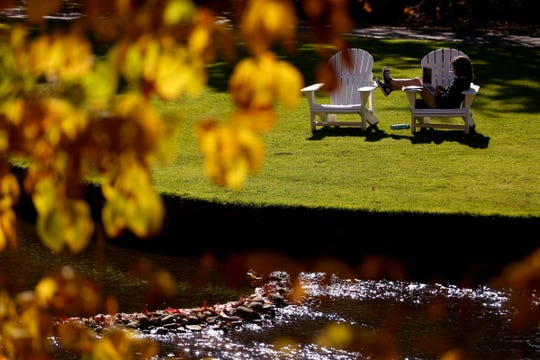 A woman works on a laptop outside at Willamette University in Salem on Wednesday, Oct. 17, 2018. Tuesday saw a high of 83 degrees in Salem, tying the record set in 2002. Sunshine is expected to continue into the weekend.
