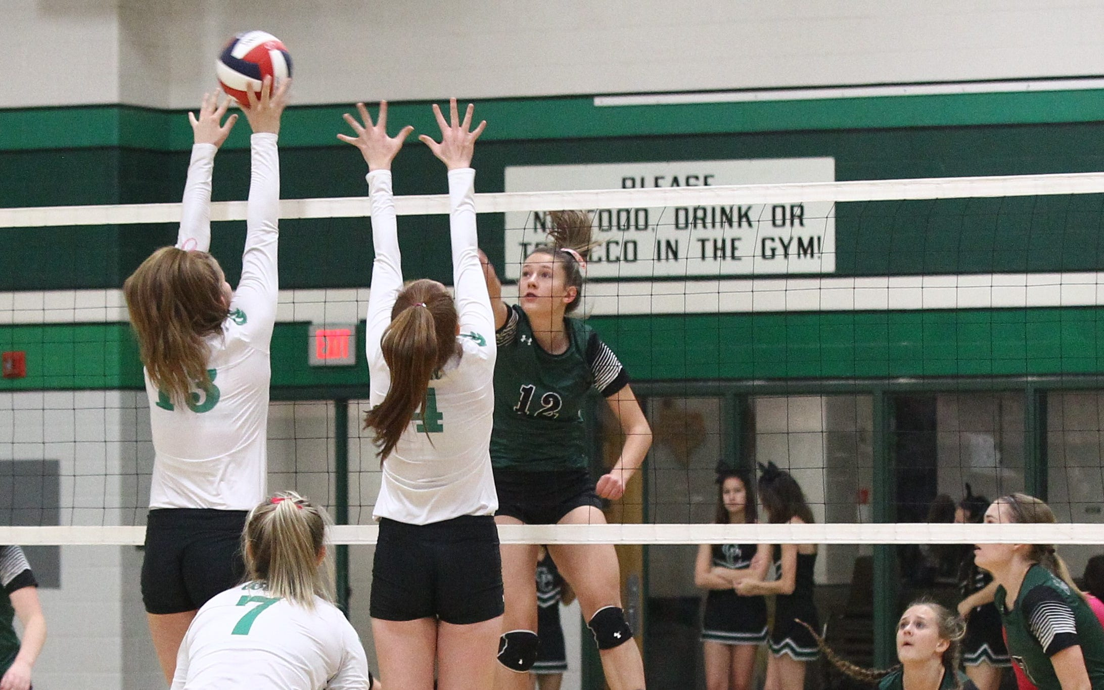 Grape Creek's Rachel Porter (12) tries to hit the ball past the block of Wall's Kaitlyn Stephens (13) and Natalie Dragt (4) in a District 4-3A volleyball match Tuesday, Oct. 16, 2018, at Wall.