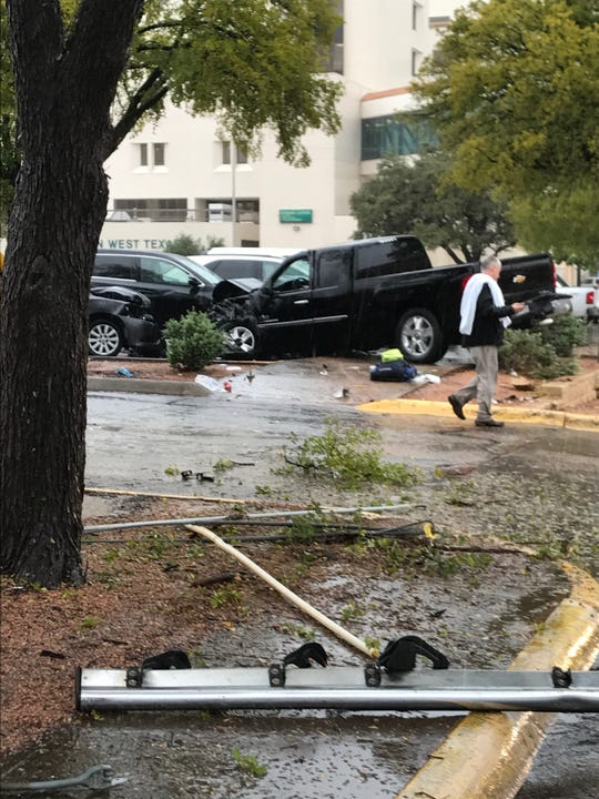 A black pickup rests half on the sidewalk and half in an occupied parking space on Tuesday, Oct. 17. The driver had a medical condition, officials said.