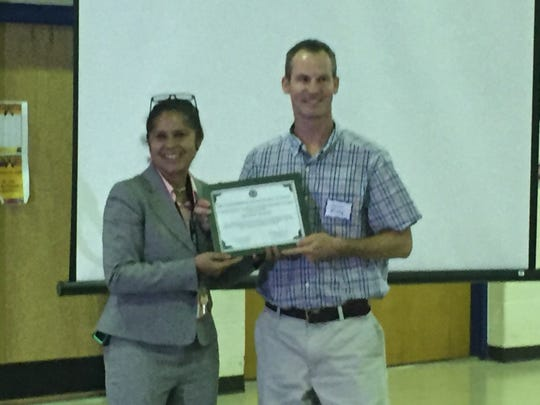 Shirley Auguste, Occohannock Elementary School principal, presents a community partner award to Jason Kirby during the State of the Schools forum in Eastville, Virginia on Tuesday, Oct. 16, 2018.