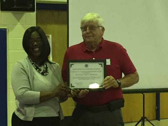 Subrina Parker, Kiptopeke Elementary School principal, presents a community partner award to Bill Prosise during the State of the Schools forum in Eastville, Virginia on Tuesday, Oct. 16, 2018.