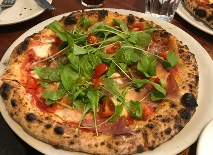 The pizza special features arugula, cherry tomatoes, thinly sliced prosciutto and fresh mozarella cheese, at Il Ritrovo, Monday, October 15, 2018, in Sheboygan, Wis. Pizza at Il Ritrovo is baked in an authentic Italian wood fired oven.