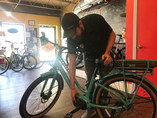 Spoke-N-Sport manager Peter Oien showcases an pedal-assisted electronic bicycle from inside the business' Minnesota Avenue store in Sioux Falls Wednesday, Oct. 17, 2018.