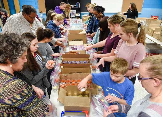 About 25 volunteers pack weekend meals for area school students by the group Feeding Area Children Together Thursday, Oct. 11, at Discovery School in Waite Park.