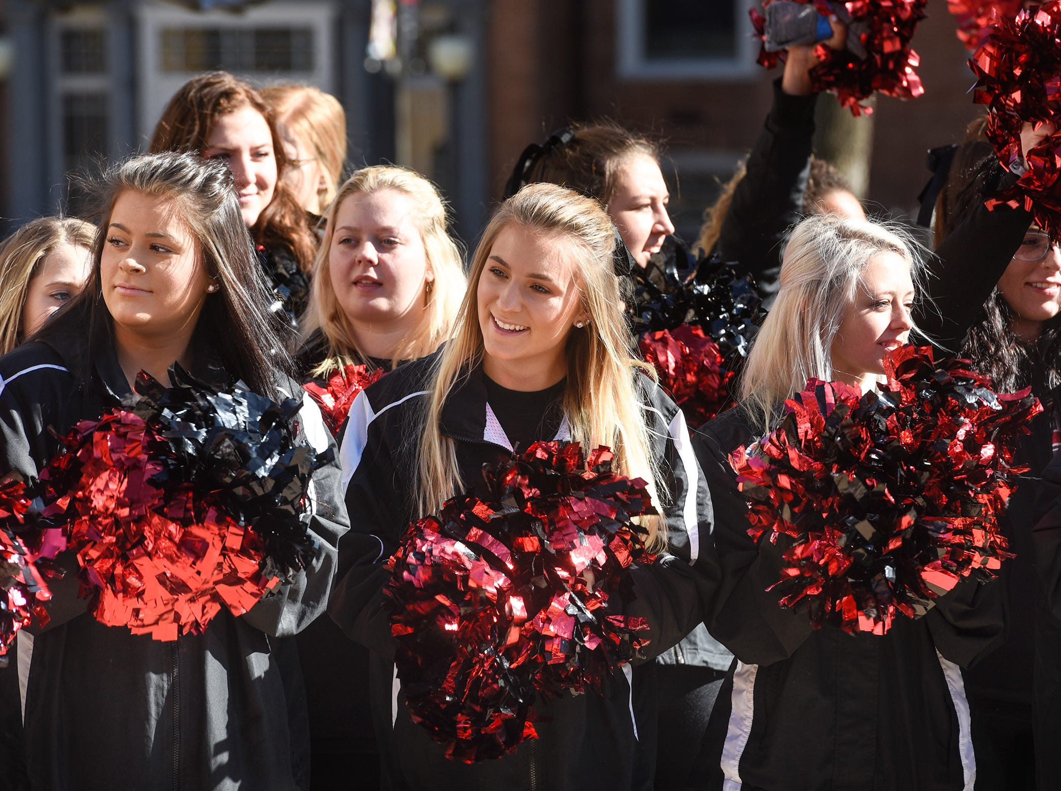 St. Cloud State University cheer team members smile during homecoming kick-off activities Wednesday, Oct. 17, at St. Cloud State University's Atwood Memorial Center Mall.