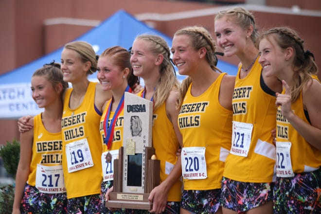 Members of the Desert Hills cross country team pose with the 4A state championship trophy in Salt Lake City on Oct. 17, 2018.