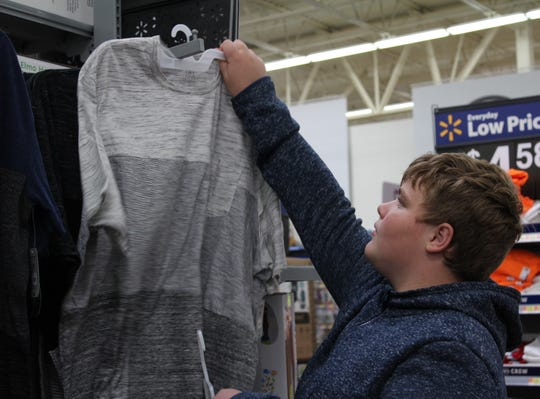 Hildale student Clay Blackmore peruses the shirt selection during Operation School Bell, a shopping event that helps kids buy clothes for school Oct. 16, 2018.