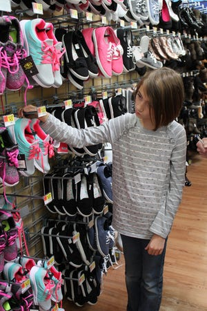 Jane Larson contemplates the shoe selection at the Hurricane Walmart during this year's Operation School Bell, Oct. 16, 2018.