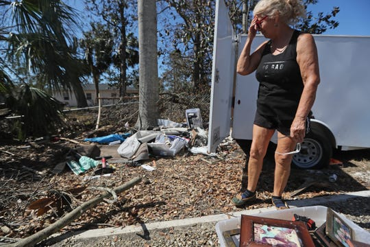 Maria Brown, who moved into a rental property with her trailer just three months before Hurricane Michael rolled through, looks over her scattered, storm drenched belongings outside of her home in Port St. Joe on Tuesday, Oct. 16, 2018.