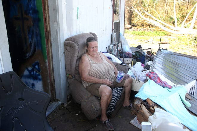 Ruby Love, a resident of Two Egg, Fla. sits on her porch while a portion of her roof also rests on the porch after Hurricane Michael on Wednesday, Oct. 17, 2018.