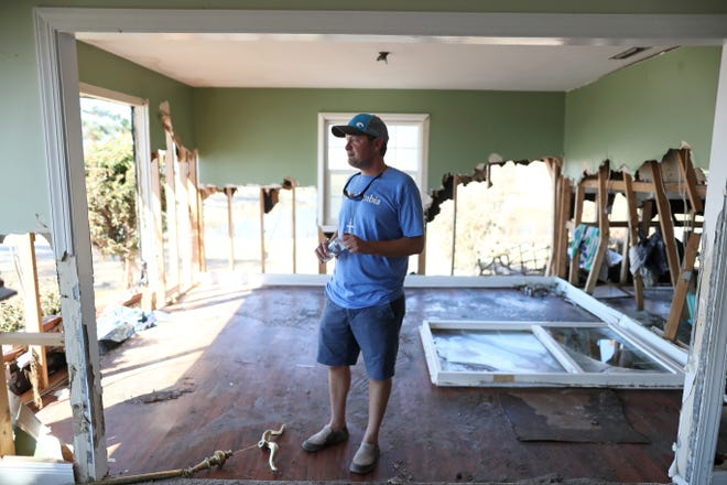 "Pastor Geoffrey Lentz stands inside his destroyed coastal home in Port St. Joe on Tuesday, Oct. 16, 2018. The Lentz family home, right outside the First United Methodist Church where Lentz leads his congregation, were left battered by Hurricane Michael's pass through the region. ""We believe in resurrection. It looks dead, gone, it's hard to see the future, but we're a people who believe in the future. Believe that the dead come back to life. And that faith sustains us,"" said Lentz."