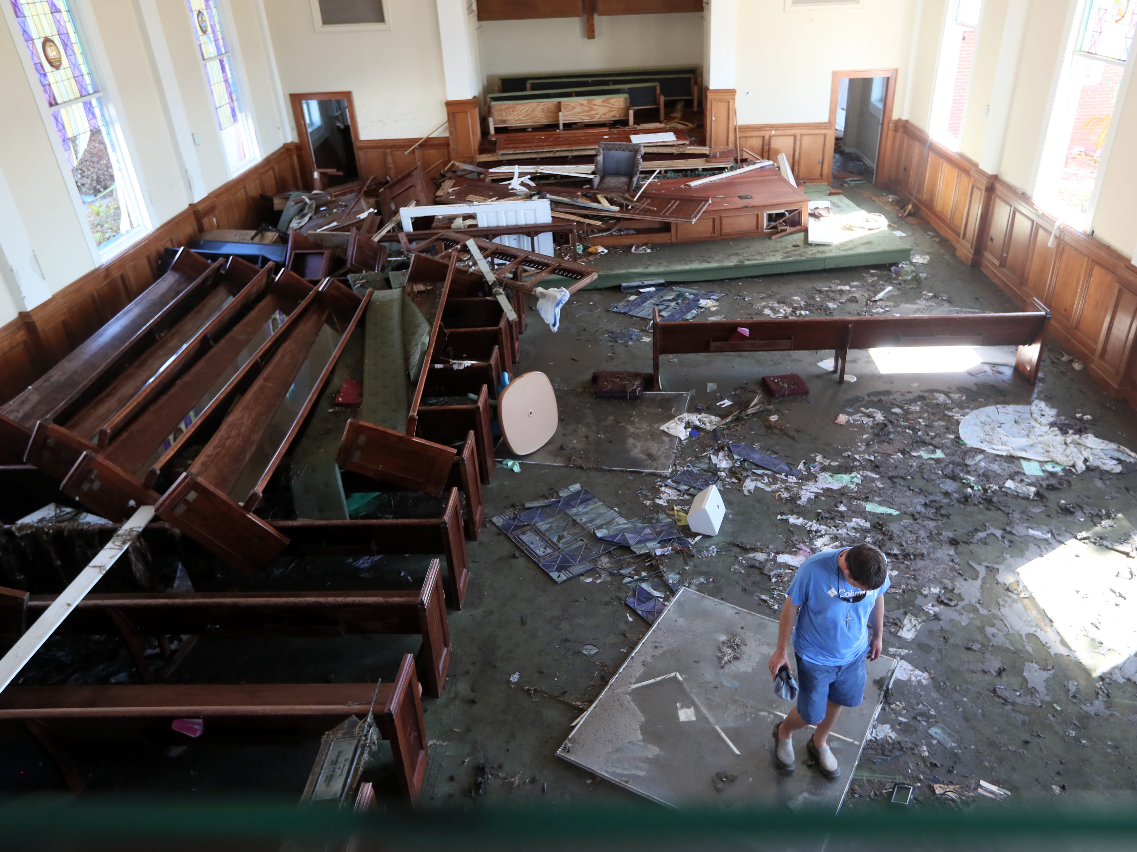 Pastor Geoffrey Lentz walks through the scattered remains of his congregation's First United Methodist Church in Port St. Joe on Tuesday, Oct. 16, 2018. The church was battered by Hurricane Michael, leaving both the sanctuary and the pastor's house in shambles.