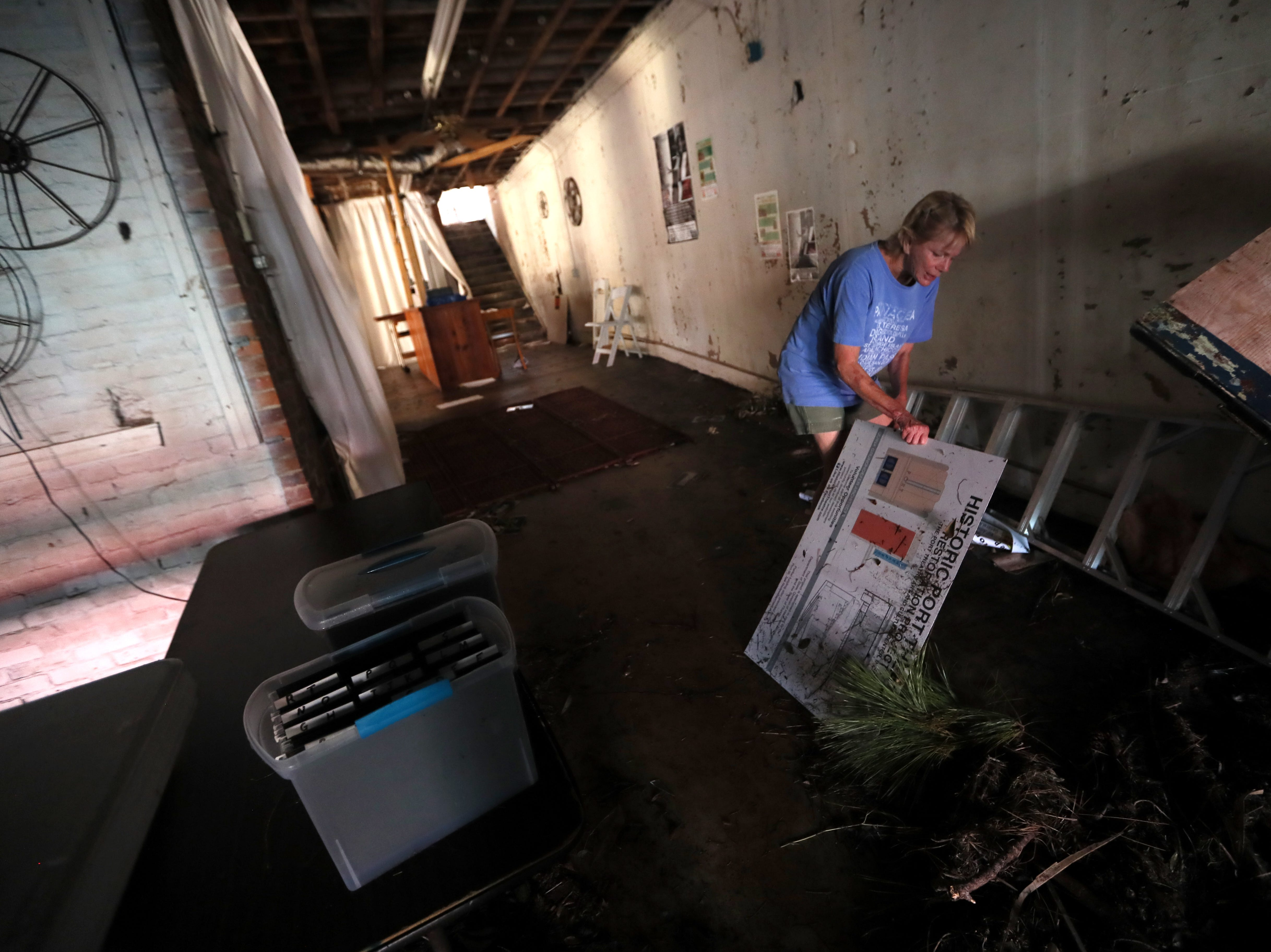 Natalie Shoaf, a member of the board of directors for the Historic Port Theatre on Reid Avenue downtown, looks in on the storm damaged space after Hurricane Michael's pass in Port St. Joe on Tuesday, Oct. 16, 2018.