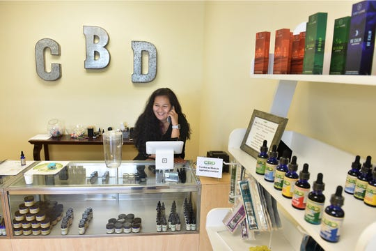 "Natalie Christianson, general manager of CBD Hemp Dropz, answers a call while working at her shop on Thursday, Oct. 11, 2018, at the Miracle Plaza, 2761 NW Federal Highway in Jensen Beach. ""There's so many different stigmas to CBD that it'll get you high, that it's snake oil. There is so many things that people don't know about CBD, and the benefits that it can do,"" Christianson said. ""It helps me with anxiety, with my depression, with my PTSD from my recovering addiction…so if there is something that can help that doesn't have to be a narcotic, or something that gets people high, why not."""