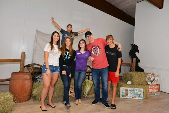 Celebrating the engagement are Kaylee Maikranz in back, Bianca Maynard, Madison Maynard, Katy Stalnaker, Ben Wilkinson and Dale Karman at the Wild Roses Foundation's Rose Buds & Country Studs workshop at River Walk Center in Fort Pierce.