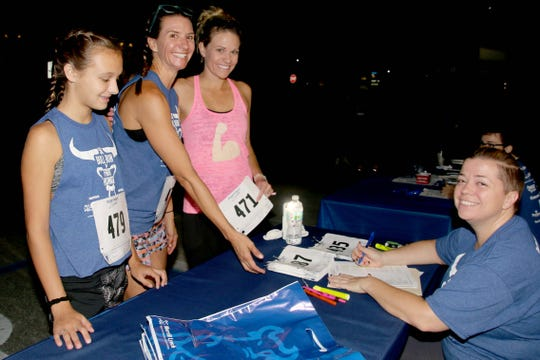 Sunny Stephan, left, Amber Stephan and Shannon Smith check in with Rachel Terlizzi the morning of the Merrill Lynch Bull Run 5K to Fight Hunger.