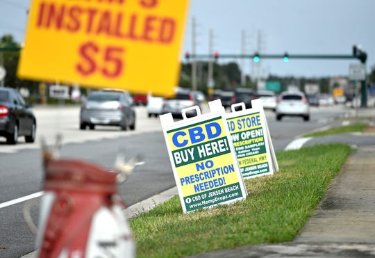 Signs for CBD Hemp Dropz are seen as northbound traffic passes by their store in the Miracle Plaza at 2761 NW Federal Highway in Jensen Beach. CBD Hemp Dropz sells products made with CBD hemp oil, used to get the medicinal properties of marijuana without the high.