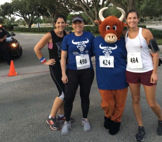 Nancy McCarthy, left, Lora duPlooy, Carol G. Houwaart-Diez (in the Bull costume) and Kelly Tullidge were three of 100 runners who participated in the Merrill Lynch Bull Run 5K.