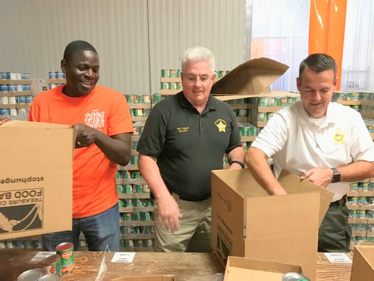 State Rep. Kim Johnson, with Pat Tighe, and Bill Lawhhorn from the St. Lucie Sheriff's Office  packed food boxes at the  2017 event.