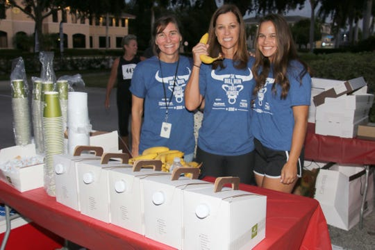 Shannon Murphy, left, Pam Dallas and Meredith Dallas make sure the refreshments are stocked so runners could refuel after the Merrill Lynch Bull Run 5K to Fight Hunger in Stuart.