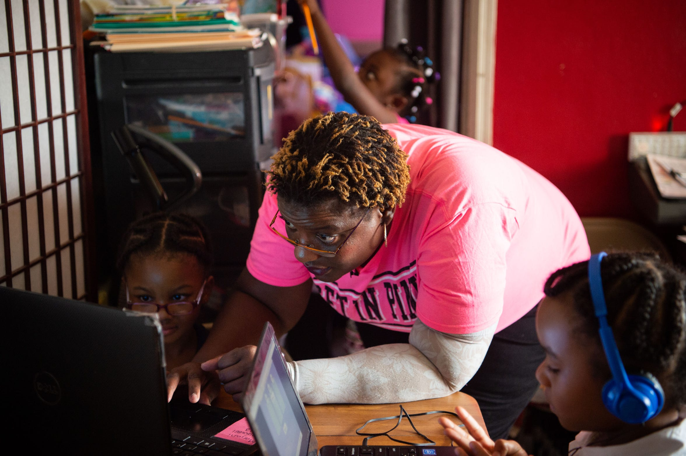 Pamela Turner, a Navy veteran and former corrections officer, helps get two of her foster children get started with schoolwork Oct. 9, 2018, at home in Fort Pierce.