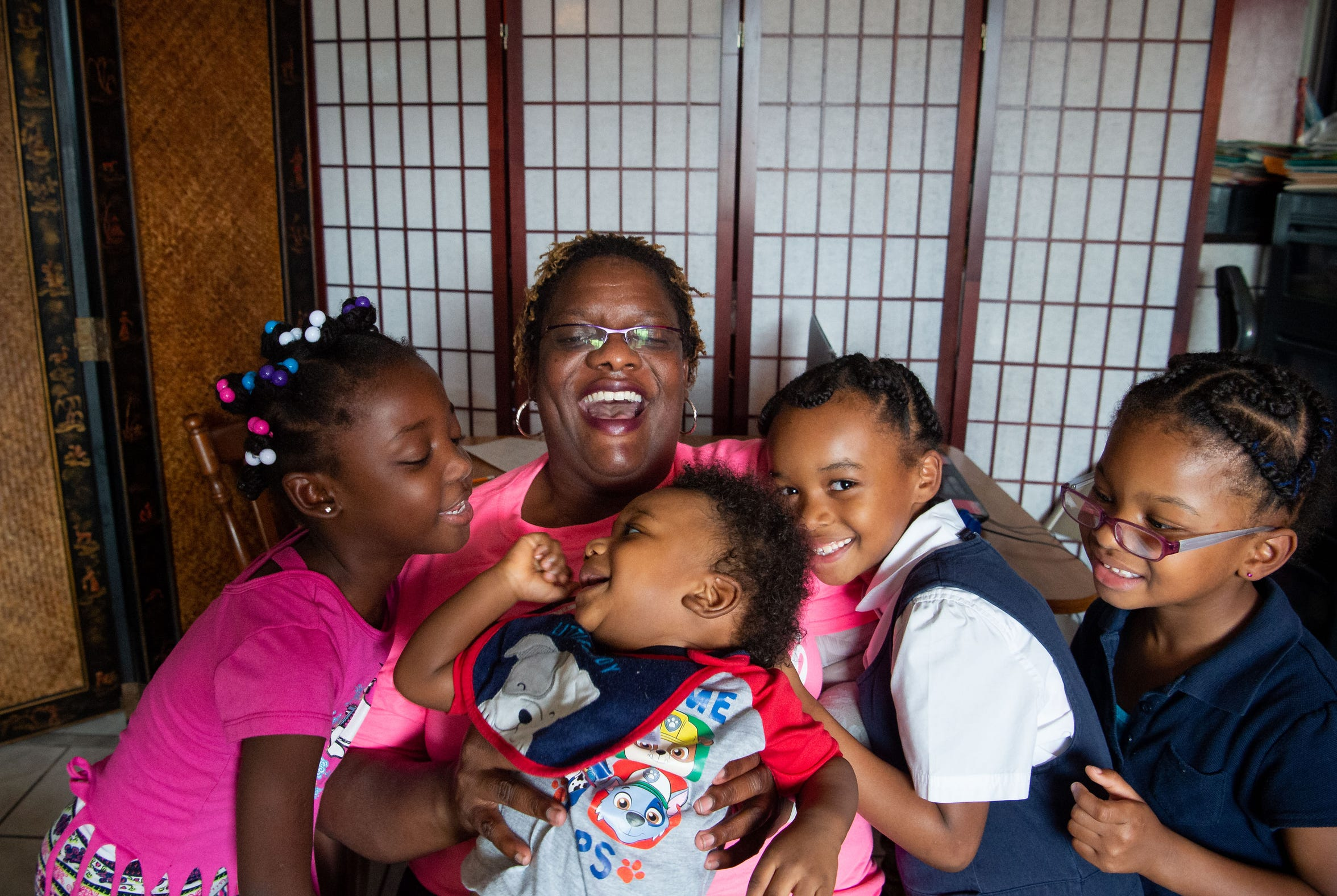"Pamela Turner — a disabled Navy veteran, cancer survivor, former corrections officer and single mother of four — poses for a family portrait with (from left) her 6-year-old biological daughter Matteo Leger, and foster children Marc Turner Jr., 1, Jahzara Turner, 6, and Marjani Turner, 5, at home Oct. 9, 2018, in Fort Pierce. Turner said something that worries her about the future of Florida is healthcare. ""I have a daughter, she has a pre-existing condition but it's covered under Florida Medicaid, but sometimes it's difficult to get certain medications because the medications cost too much money...you have to learn how to do research to find out what methods you have available to use."""